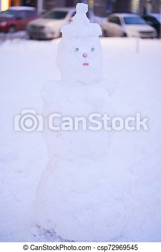 cute snowy snowman in the evening at the christmas city with nobody - csp72969545