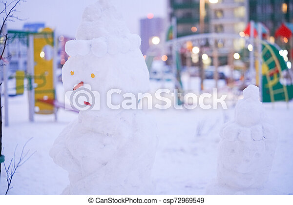 cute snowy snowman in the evening at the christmas city with nobody - csp72969549