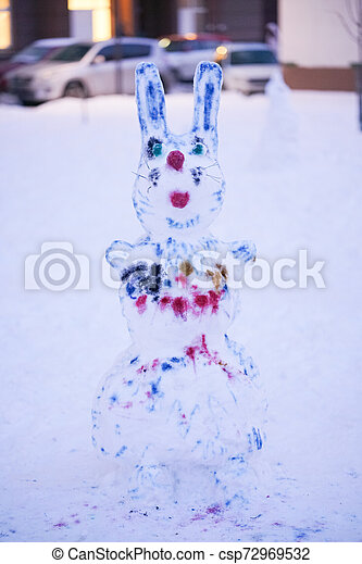 cute snowy snowman in the evening at the christmas city with nobody - csp72969532