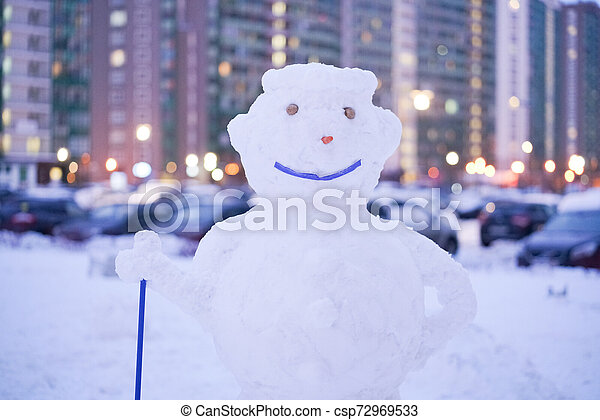 cute snowy snowman in the evening at the christmas city with nobody - csp72969533