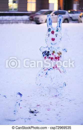 cute snowy snowman in the evening at the christmas city with nobody - csp72969535