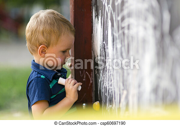 Cute toddler drawing with chalk outdoors - csp60697190