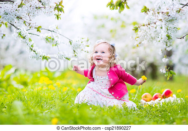 ffdd5710daf Cute toddler girl eating apple in a blooming garden. Adorable happy ...