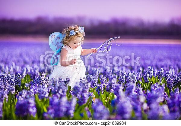 Cute toddler girl in fairy costume in a flower field - csp21889984