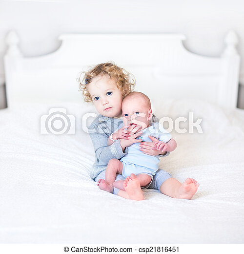 Cute toddler girl playing with her newborn baby brother - csp21816451