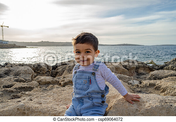 cute two years old boy sitting on the rocks on the sea - csp69064072