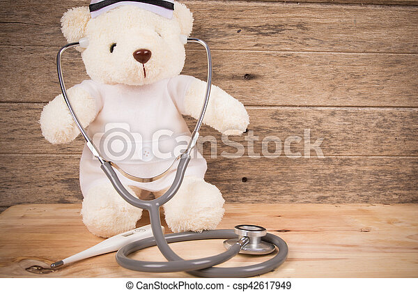 Cute white tebby bear wear nurse with stethoscope and thermometer on wooden background ,vintage tone - csp42617949