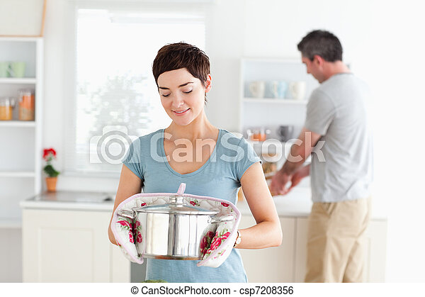 Cute Woman holding a pot while man is washing the dishes - csp7208356