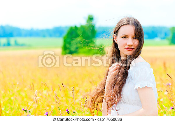cute woman resting in a field with flowers - csp17658636