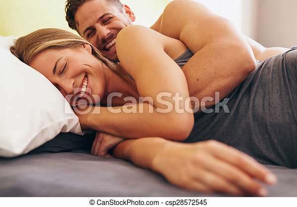 Cute young couple in love lying on bed - csp28572545