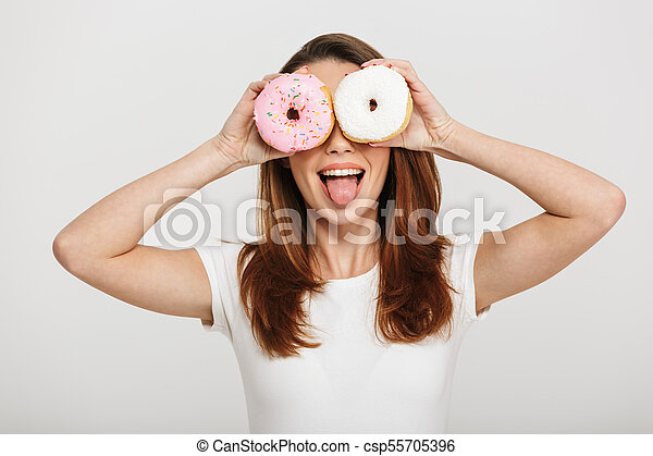 Cute young woman standing holding donuts in front of eyes. - csp55705396