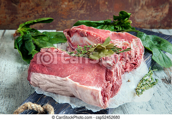 Cuts of beef for grilling on a wooden cutting Board with spinach, rosemary and Provencal herbs for the marinade in a rustic style. - csp52452680