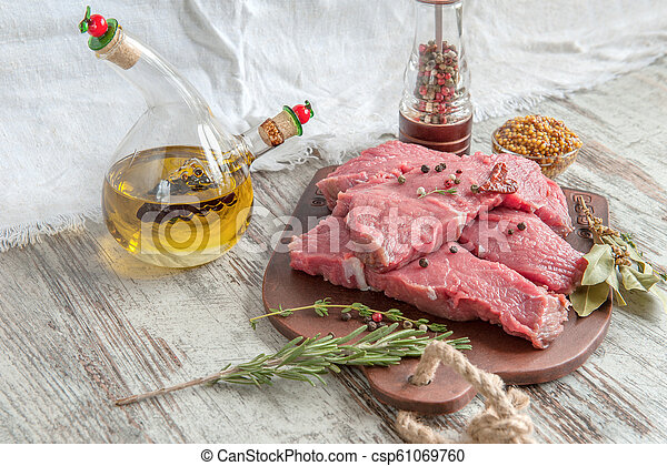 Cuts of beef for grilling on a wooden cutting Board with the Bay leaf, rosemary, olive oil and Provencal herbs for the marinade in a rustic style - csp61069760