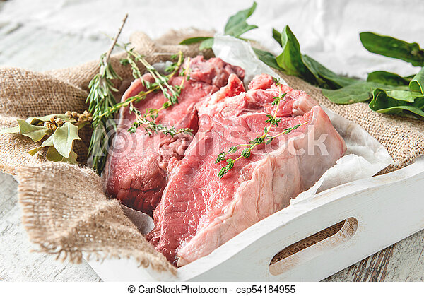 Cuts of beef for grilling on a wooden cutting Board with spinach, rosemary and Provencal herbs for the marinade in a rustic style. - csp54184955