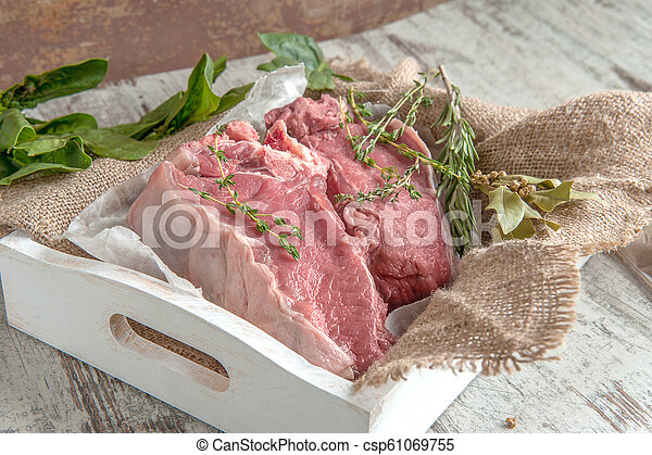Cuts of beef for grilling on a wooden cutting Board with spinach, rosemary and Provencal herbs for the marinade in a rustic style - csp61069755