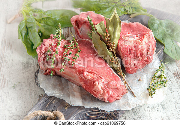 Cuts of beef for grilling on a wooden cutting Board with spinach, rosemary and Provencal herbs for the marinade in a rustic style - csp61069756