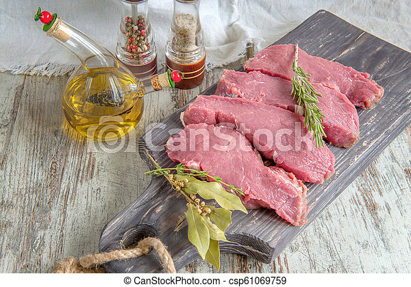 Cuts of beef for grilling on a wooden cutting Board with the Bay leaf, rosemary, olive oil and Provencal herbs for the marinade in a rustic style - csp61069759