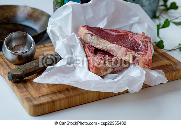 Cuts of raw beef on the cutting board with some green salad in t - csp22355482