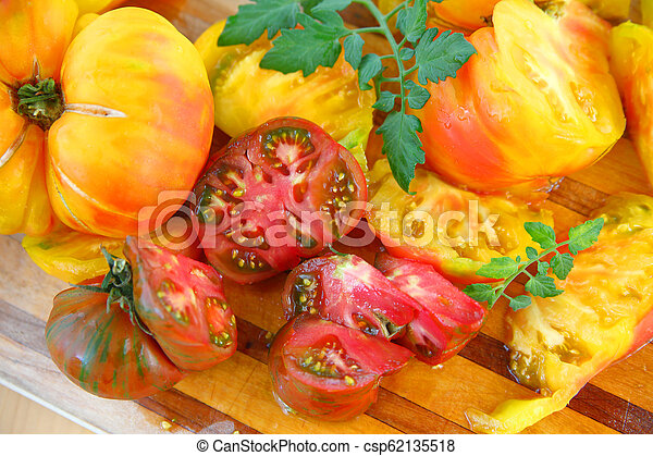 Cutting board with assorted heirloom tomatoes - csp62135518