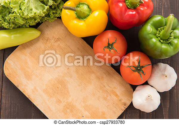 Cutting board with vegetables on wooden background. - csp27933780
