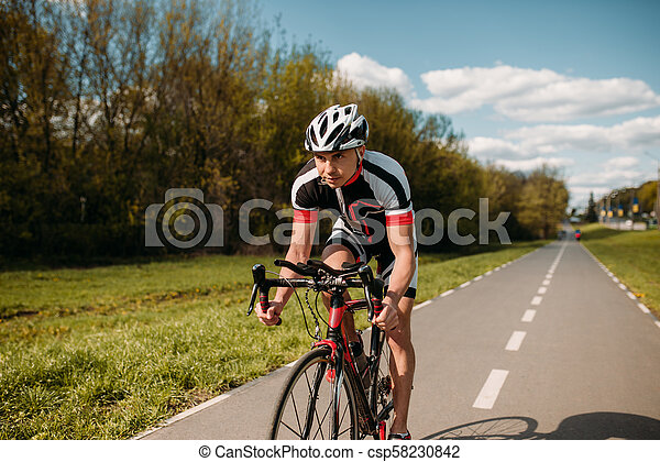 Cyclist in helmet and sportswear, bicycle training - csp58230842