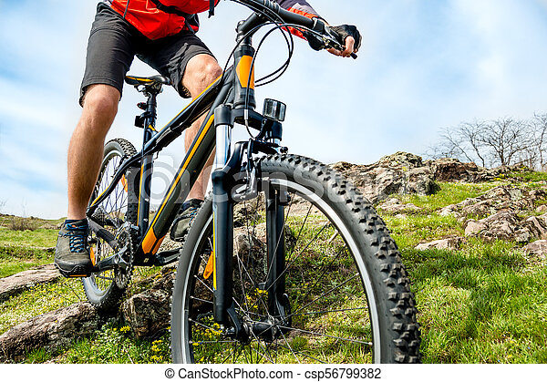 Cyclist in Red Jacket Riding Mountain Bike Down Rocky Hill. Extreme Sport and Adventure Concept. - csp56799382