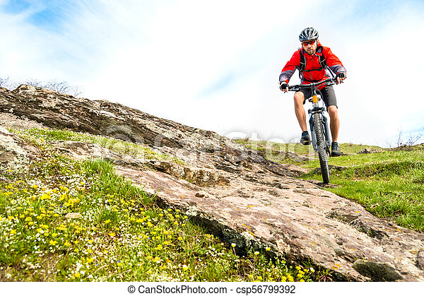 Cyclist in Red Jacket Riding Mountain Bike Down Rocky Hill. Extreme Sport and Adventure Concept. - csp56799392