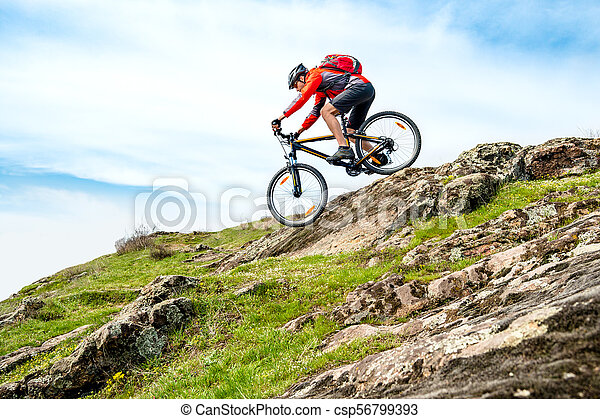 Cyclist in Red Jacket Riding Mountain Bike Down Rocky Hill. Extreme Sport and Adventure Concept. - csp56799393