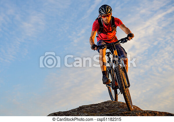 Cyclist in Red Riding the Bike Down the Rock on the Blue Sky Background. Extreme Sport and Enduro Biking Concept. - csp51182315