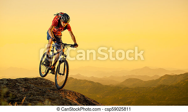 Cyclist in Red Riding the Bike Down the Rock at Sunset. Extreme Sport and Enduro Biking Concept. - csp59025811