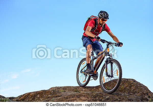 Cyclist in Red Riding the Bike Down the Rock on the Blue Sky Background. Extreme Sport and Enduro Biking Concept. - csp51046651