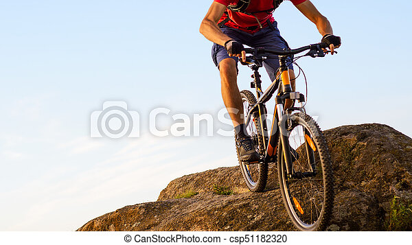 Cyclist in Red Riding the Bike Down the Rock on the Blue Sky Background. Extreme Sport and Enduro Biking Concept. - csp51182320
