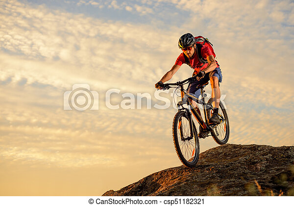 Cyclist in Red Riding the Bike Down the Rock at Sunset. Extreme Sport and Enduro Biking Concept. - csp51182321