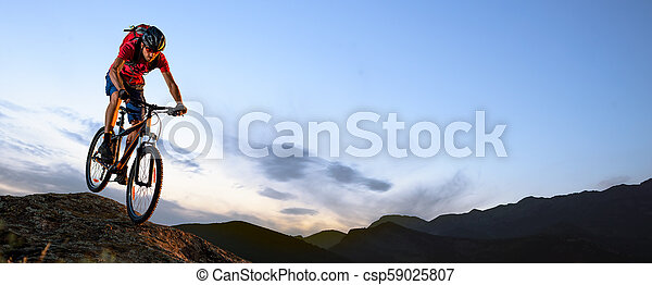 Cyclist in Red Riding the Bike Down the Rock at Sunset. Extreme Sport and Enduro Biking Concept. - csp59025807