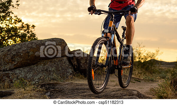 Cyclist in Red Riding the Bike on the Rocky Trail at Sunset. Extreme Sport and Enduro Biking Concept. - csp51182313