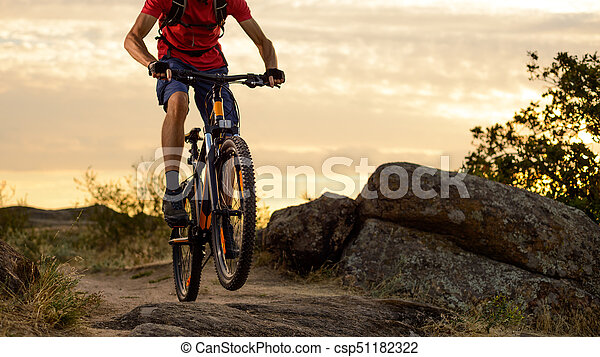 Cyclist in Red Riding the Bike on the Rocky Trail at Sunset. Extreme Sport and Enduro Biking Concept. - csp51182322