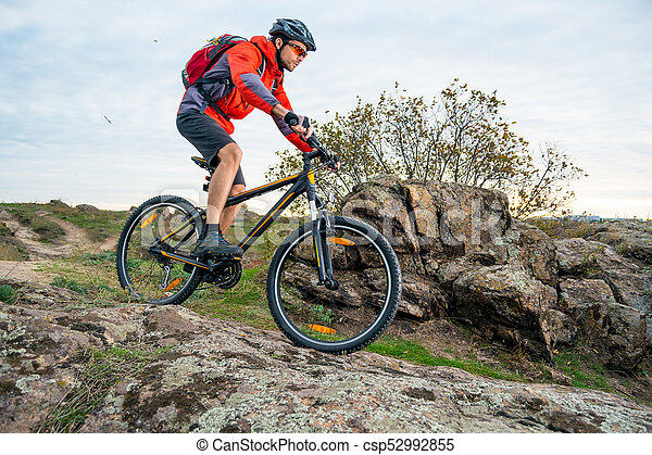 Cyclist in Red Riding the Mountain Bike down Autumn Rocky Trail. Extreme Sport and Enduro Biking Concept. - csp52992855