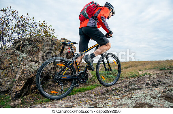 Cyclist in Red Riding the Mountain Bike up Autumn Rocky Trail. Extreme Sport and Enduro Biking Concept. - csp52992856