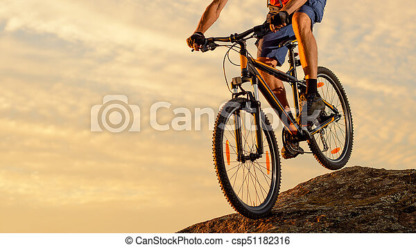 Cyclist Riding the Bike Down the Rock at Sunset. Extreme Sport and Enduro Biking Concept. - csp51182316