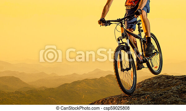 Cyclist Riding the Bike Down the Rock at Sunset. Extreme Sport and Enduro Biking Concept. - csp59025808