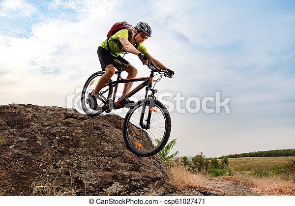 Cyclist Riding the Bike on Autumn Rocky Trail at Sunset. Extreme Sport and Enduro Biking Concept. - csp61027471