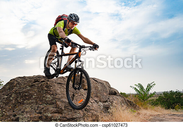 Cyclist Riding the Bike on Autumn Rocky Trail at Sunset. Extreme Sport and Enduro Biking Concept. - csp61027473