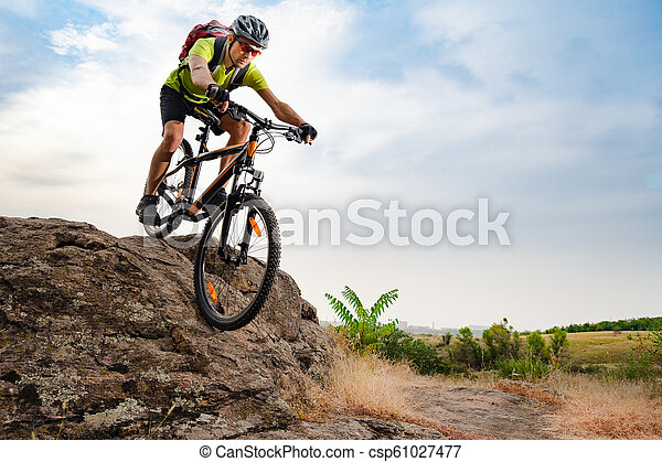 Cyclist Riding the Bike on Autumn Rocky Trail at Sunset. Extreme Sport and Enduro Biking Concept. - csp61027477