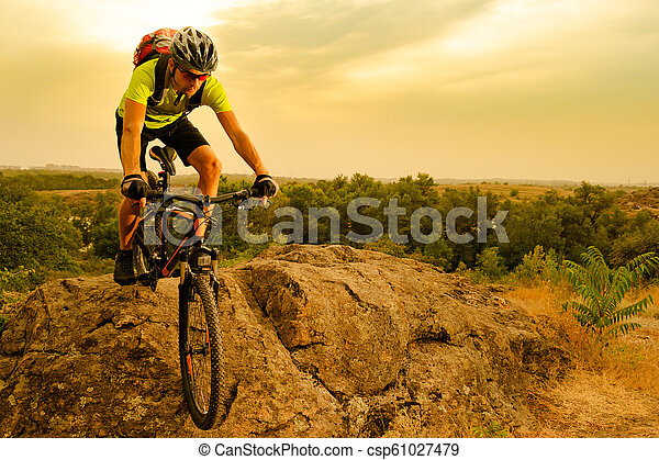 Cyclist Riding the Bike on Autumn Rocky Trail at Sunset. Extreme Sport and Enduro Biking Concept. - csp61027479