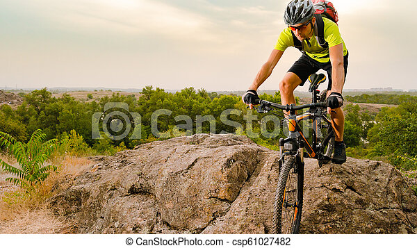 Cyclist Riding the Bike on Autumn Rocky Trail at Sunset. Extreme Sport and Enduro Biking Concept. - csp61027482