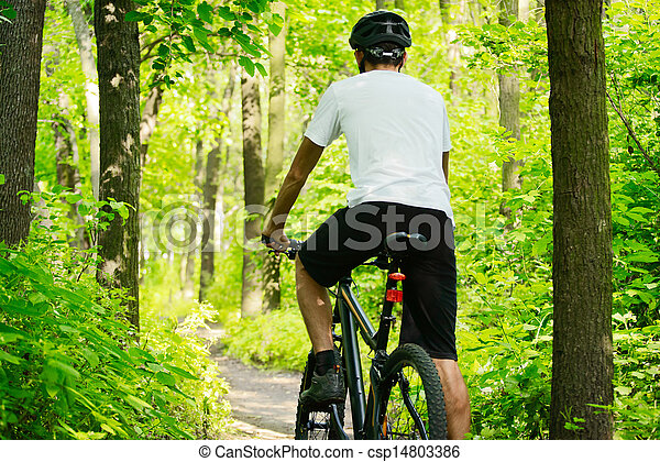 Cyclist Riding the Bike on the Trail in the Forest - csp14803386