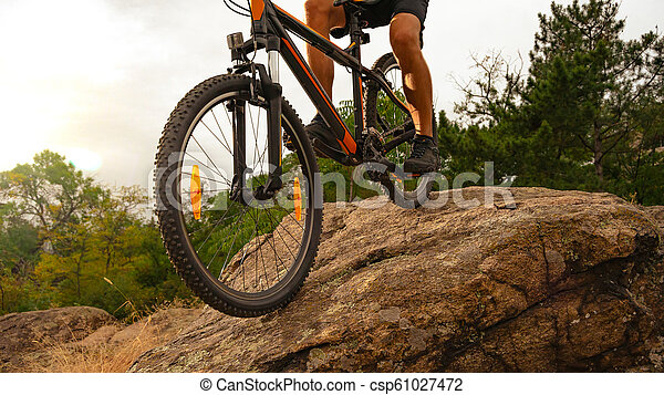 Cyclist Riding the Mountain Bike Down the Rock at Sunset. Extreme Sport and Enduro Biking Concept. - csp61027472