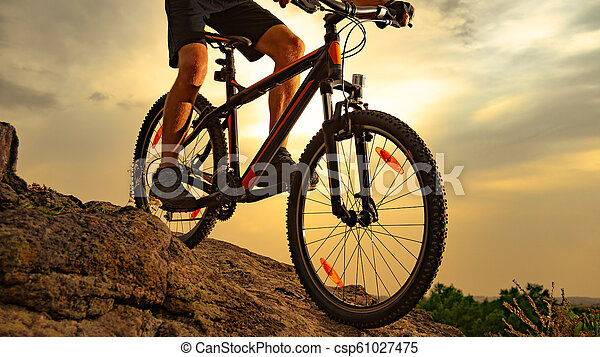 Cyclist Riding the Mountain Bike Down the Rock at Sunset. Extreme Sport and Enduro Biking Concept. - csp61027475