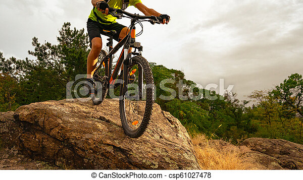 Cyclist Riding the Mountain Bike Down the Rock at Sunset. Extreme Sport and Enduro Biking Concept. - csp61027478
