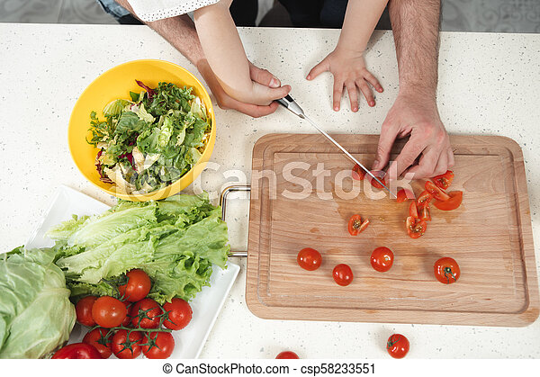 Dad and kid making salad in kitchen - csp58233551